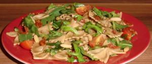 Nudelsalat mit Rucola, getrockneten Tomaten, Cherrytomaten und Pinienkernen